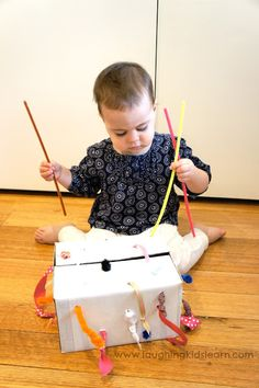 Simple box with ribbons that lengthen and shorten as pulled is this DIY tugging box for fine motor development. Never-ending fun for young children.