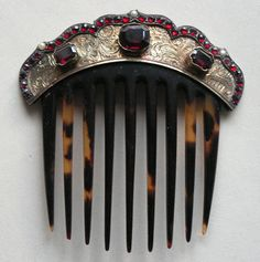 This garnet comb is a tortoiseshell backcomb with silver gilt heading. The surface is engraved with Renaissance-style scrolling designs and set with large- and small-faceted garnets and 3 small pearls. English 1840-60. L = 3½ ins (8.9 cm); W = 3¼ ins (8.2 cm).