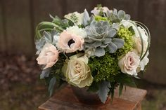 Modern centerpiece with succulents, peach anemones, green hydrangea, roses, dusty miller and lily grass, by Cincinnati wedding florist Floral Verde.
