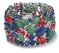 Bracelet CARTIER PARIS, 1929 Platinum, brilliant- and single-cut diamonds, leaf-shaped carved sapphires, emeralds and rubies, emerald and sapphire cabochons, ruby beads studded with collet-set diamonds.  18.0 x 4.07 x 0.75 cm