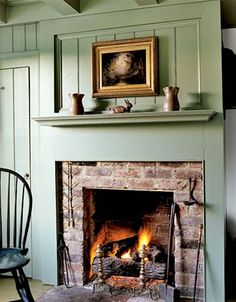 Build a mantel around brick fireplace. sage green raised panel wall reveals a simple brick fireplace in this home. Antique pottery is displayed on the mantel. Country Fireplace, Cozy Fireplace, Fireplace Surrounds, Fireplace Design, Fireplace Mantels, Cottage Fireplace, Mantles, Fireplace Ideas, Farmhouse Fireplace