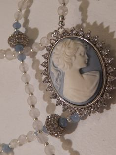 Something Blue Wedgewood Blue Bridal Rosary •	Decade beads opulent Semi-Precious gorgeous White Rock Crystal Gemstones (6mm) •	Our Father beads stunning Crystal Encrusted Roundelles accented with Pale Blue Faceted Glass beads •	Sterling Silver round beads beautifully sprinkled throughout compliment the beauty of this piece •	Wedgewood Blue style Cameo Center