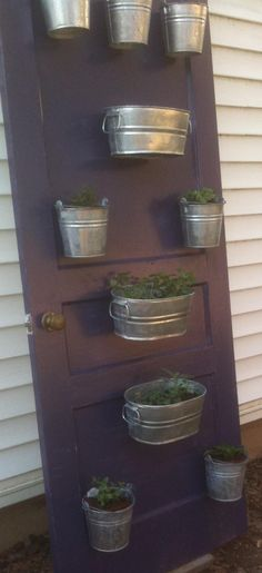 One old door + leftover paint + assorted galvanized buckets = vertical herb garden for a small space.