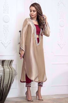 A loose fit kaftan style tunic is formal yet has a cool vibe to it. Hand work silver embroidery on neckline and sleeves on a rich gold tissue shirt. Simple Pakistani Dresses, Pakistani Fashion Casual, Indian Fashion Dresses, Dress Indian Style, Pakistani Dress Design, Fashion Outfits, Pakistani Designer Clothes, Muslim Fashion, Stylish Dress Designs