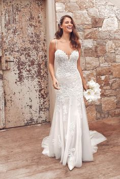 Accentuate your shape in this embroidered lace fit and flare gown. The bikini neckline features a slight plunge with beaded spaghetti straps. Beading throughout the gown adds the perfect amount of sparkle. Buttons extend down the cascading chapel length train.