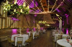 Huge warm white gathered fairy light canopy in the barn at Lillibrooke with deep pink uplighting