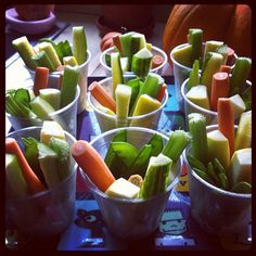 Veggie cups with scoops of dip at the bottom.
