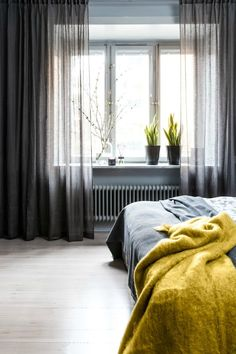 mood grey master bedroom design with plants on windowsil and yellow felt throw on end of bed