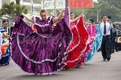Hay bailarines con los vestidos en el desfile. Niños charlan y juegan con los parientes.