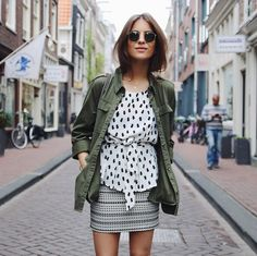 Lizzy van der Ligt wears a relaxed army jacket over a dotted blouse and printed mini skirt with Ray-Ban sunglasses
