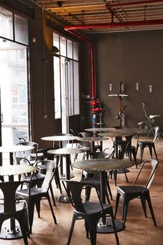 Steel cog tables and iconic holix stools, contrasted with vivid red steel piping