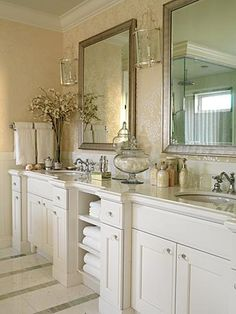 Beautiful traditional bathroom design with gold yellow Romo sapporo oval metallic wallpaper, beveled antique silver mirrors, lantern sconces, marble countertops, ivory cream bathroom cabinets, glass knobs hardware, crown molding and marble tiled floors. white ivory cream yellow gold bathroom colors