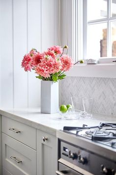 White kitchen cabinets adorning polished nickel pulls and topped with a white quartz countertop are accented by a white marble chevron backsplash fixed beneath a window and above a stainless steel oven range.