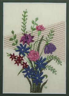 "Floral on Linen - 2651  This advanced piece is worked on 25 count ivory linen.  First the background is worked with a pulled thread pattern, then a spray of Brazilian embroidery flowers is added. There are detached and attached needle-woven petals, and some double cast-on bullion combination stitches used.  The design fits a 5"" x 7"" mat or frame.     $14.00"