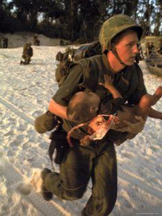 US Marine Medic Running Along Beach with Injured Vietnamese Infant under Fire During Vietnam War