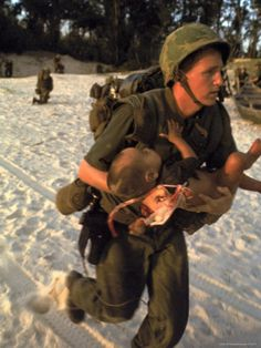 US Marine Medic Running Along Beach with Injured Vietnamese Infant under Fire During Vietnam War