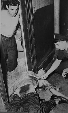 August Anthony Krzesinski lies dead in the hallway of a bulding where he ran after being attacked by Salvador Agron,Antonio Hernandez and other gang members.A patrolman points to a stab wound in the body.