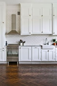 Oh I love so much here-- white subway tile and cupboards to the ceiling, range hood and the dark chevron wood floors!