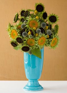 Love that aqua vase with the colors in the flower arrangement