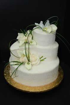 Wedding cake with a tear drop tier. Crystal sugar coated to give it a sparkly look. Accented with fresh calla lilies and roses. www.sugarhillsbakery.com