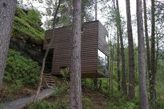 The cabins by Jensen & Skodvin Architects are built on a steep hillside. They're held aloft by narrow steel rods and clad in a lumber that's stained to blend into the natural surroundings.