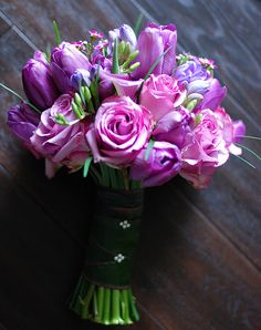 A purple-theme bouquet: roses, tulips, calla lilies, freesias, wax flowers, and lily grasses.