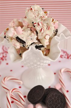 Peppermint Cookie Bark.  Oreo cookies dipped in White Chocolate. Pink Marshmallows and crushed Peppermint Candy are pressed in after dipping. Yum!