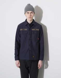 Buds Long Sleeve Shirt from WTAPS. Made in a cotton twill with two buttoned flap chest pockets. Finished with branded buttons and woven WTAPS logo tabs.  Available in Navy and Olive 100% Cotton Made in Japan  Model is 194 cm long and measures 48 cm over the shoulders and wears a size L.