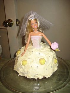 """""""...technical details of how she executed this, but it involved snapping off Barbie's legs and baking a from-scratch """"skirt"""" in an aluminum bowl. And let me tell you, the dress tasted just as good as it looked! After I cut and served the cake, Barbie was dusted off and her legs and wedding gown reattached so I could take her home as a souvenir. I think I'll give her to my flower girl on the wedding day so she'll have something new to play with."""" """"My grandma used to make those cakes for the…"""