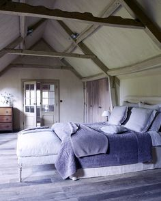 Rustic bedroom reclaimed wood floors, pitched ceiling with exposed beams. Very cozy. http://cococozy.com