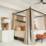 """""""We're both tall people so we had this bed made to better fit us,"""" Devi says of their custom bed. To complete their bed, they also had a four-poster headboard and footboard with canopy and privacy drapes made to give the couple extra coziness. 