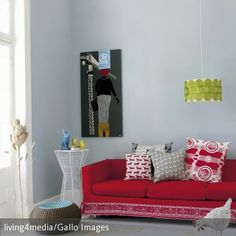 Die rote Couch, der weiße Beistelltisch und die blaue Wand sorgen ...