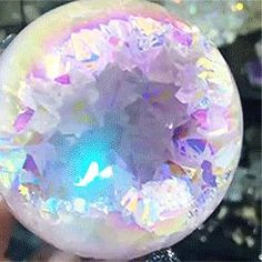 "Angel aura geode sphere' Apparently ""the gem in the gif  is Rainbow Quartz. (it's an alternative name to titanium quartz) it's created by adding a coating to normal quartz.""  (https://www.reddit.com/r/interestingasfuck/comments/4d3jps/angel_aura_geode_sphere/)"