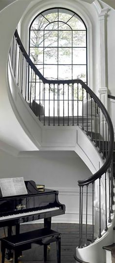Elegance and luxury combine to form a sophisticated classical interior. Curved staircase/entry with a baby grand piano. Sweet!