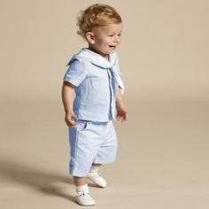 Boys pale blue two piece short and top set by Little Darlings. In a sailor suit style, the top has a classic collar with white trim and fabric covered buttons at the front with the designer's crest logo appliquéd on the chest. The matching herringbone cotton trousers are in a pull-on style with an elasticated andadjustable waist. They have turn-ups and a pouch pocket at the front.  Model: Height 78cm (average 1 year) Size of suit shown in the photo: 12 month