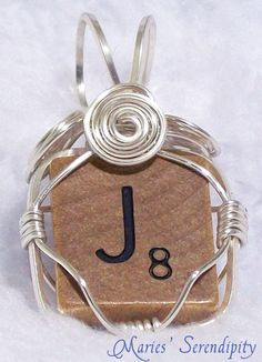 Genuine wood Scrabble Tile wrapped in silver-fill wire. Hand crafted. (While this is one of a kind, similar pendants can be made with other letters. Each will be slightly different in wrap style. Price of Scrabble pendants is $10 plus $1 per value of the letter - letters worth 1 point cost $11, letters worth 10 points cost $20. This is due to the rarity of those letters.)