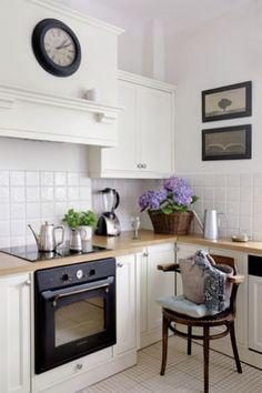 Kuchnia na biało - Joanna - projektantka - sama wymyślila szafki, a stól i krzesłą znalazła na starociach. szafki kuchenne, biel, białe meble, zegar, stylowy piekarnik, styl retro, aranżacja kuchni