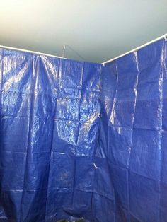 My 10' x 10' spray paint tent in the garage. I hung 4 10' sections of pvc pipe from the ceiling then attached shower curtain clips to the tarps & hung on the pvc. I can slide it open & closed or shut myself all the way in.