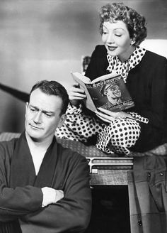 Claudette Colbert reading to John Wayne in Without Reservations, 1946. Kit Madden is traveling to Hollywood, where her best-selling novel is to be filmed. Aboard the train, she encounters Marines Rusty and Dink, who don't know she is the author of the famous book, and who don't think much of the ideas it proposes. She and Rusty are greatly attracted, but she doesn't know how to deal with his disdain for the book's author.