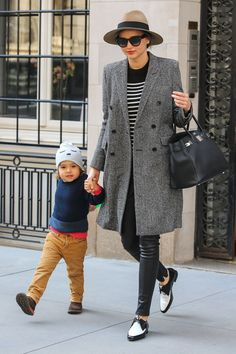 Miranda Kerr: grey coat, black leather pants, striped top, black and white shoes, Hermes bag and a hat