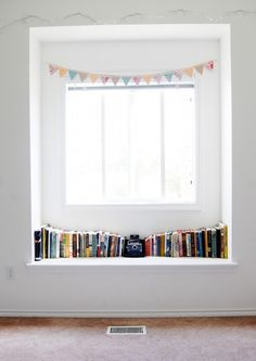 lovely window shelf with books, vintage camera and paper bunting