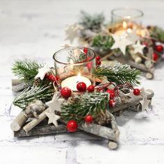 Ein dekoratives Gesteck für die Adventszeit in Sternform, geschmückt mit Zweigen, Zapfen, Holzsternen und Glitzerschnee. In der Mitte ist ein Glas für Teelichter oder kleine Kerzen. #Advent #Dekoration