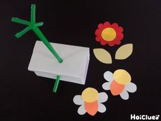 ストローを刺した空き箱と色画用紙を切り抜いたお花とミツバチの写真