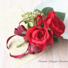 美しい赤い薔薇のブートニアタイプのコサージュです。赤い薔薇をメインに、薔薇の葉、シキミアなどでアレンジしています。リボンは、ワイヤー入りのワッシャー加工のされたビロードタイプです。素敵なインポートリボンです。お花の裏面は、茎の部分に安全ピンを取り付けてありますので、やや斜めに胸元に挿してお使いください。ウェディングはもちろん、フォーマルな場などにどうぞ♡発送の際は、大切に箱に納めて、お届けいたします