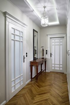 Bright Corridor With Wooden Side Table On Parquet Floor  And Decorative Mirror Also White Doors Adorned With Fascinating Ceiling Lamp Design Apartment Interior Art Deco with Lots of Intriguing Details Apartment http://seekayem.com