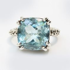 Blue topaz faceted cushion ring in silver bezel and prongs setting with sterling silver texture oxidized band Free resizing  Gemstone measure:12 mm W x 12 mm H  ~Shipping Note~ ***All items will ship by FedEx international shipping. Expected delivery times are between 3-5 days.