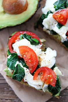Avocado Toast with Eggs, Spinach, and Tomatoes Recipe on twopeasandtheirpod.com This simple and healthy avocado toast is great for breakfast, lunch, or dinner! You have to try it!
