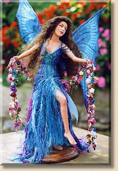 Dancing Fairy A beautiful longhaired fairy with blue wings and dress, dances through the garden with her garland of flowers. - by Martha & Marianne