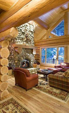 Summit Handcrafted Log river rock fireplace, red furniture, dark sq coffee table contrast light round logs, love big windows