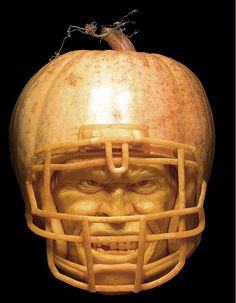 Pumpkin carved to look like it's wearing an American Football helmet